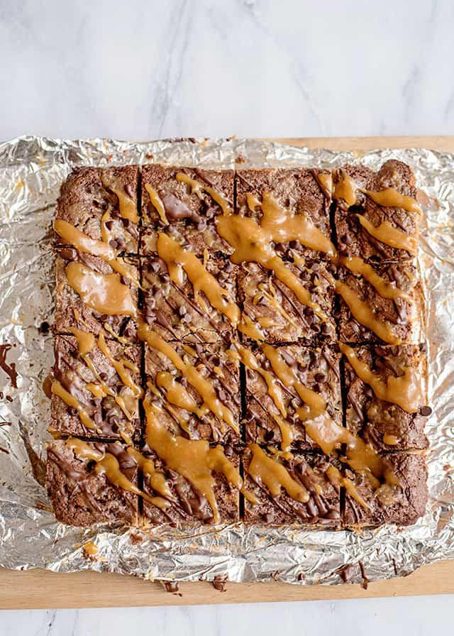cut caramel brookies on tin foil on a cutting board