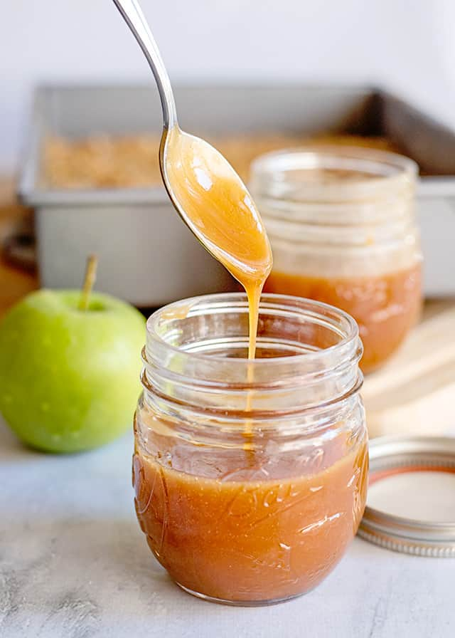 caramel dripping a spoon into a glass jar with an apple behind it