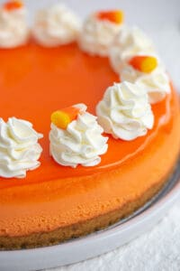 cheesecake showing the candy corn glaze and whipped cream on top