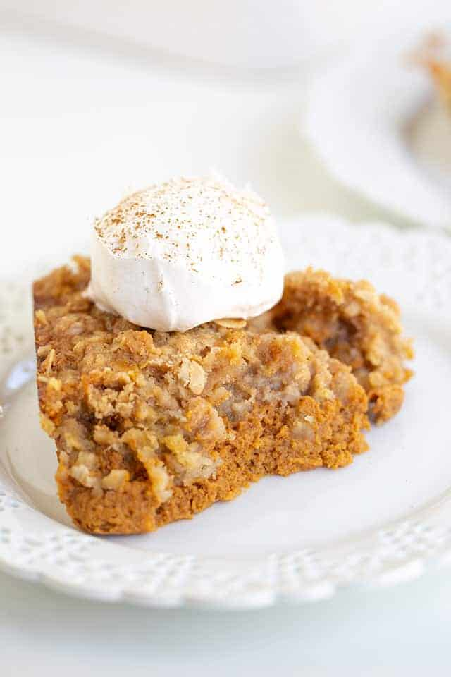 close up of pumpkin crisp with whipped cream and a dusting of cinnamon on top