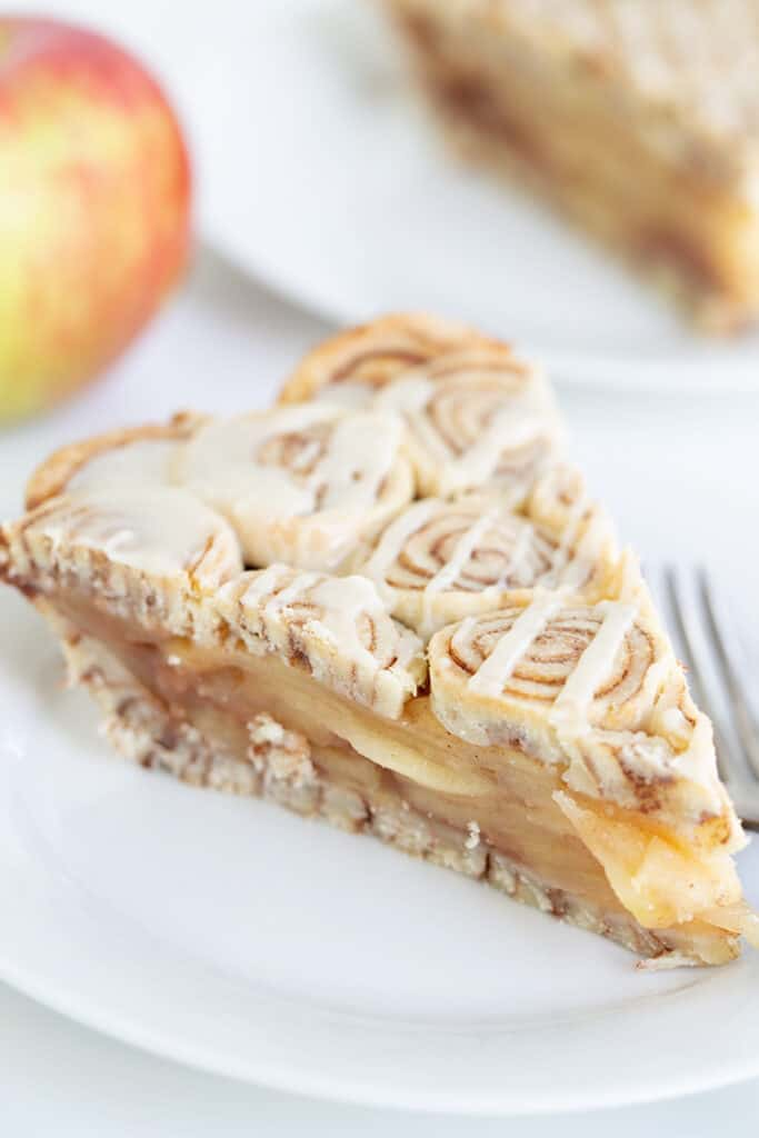 slice of apple pie on a white plate with an apple behind it and a second slice of apple pie
