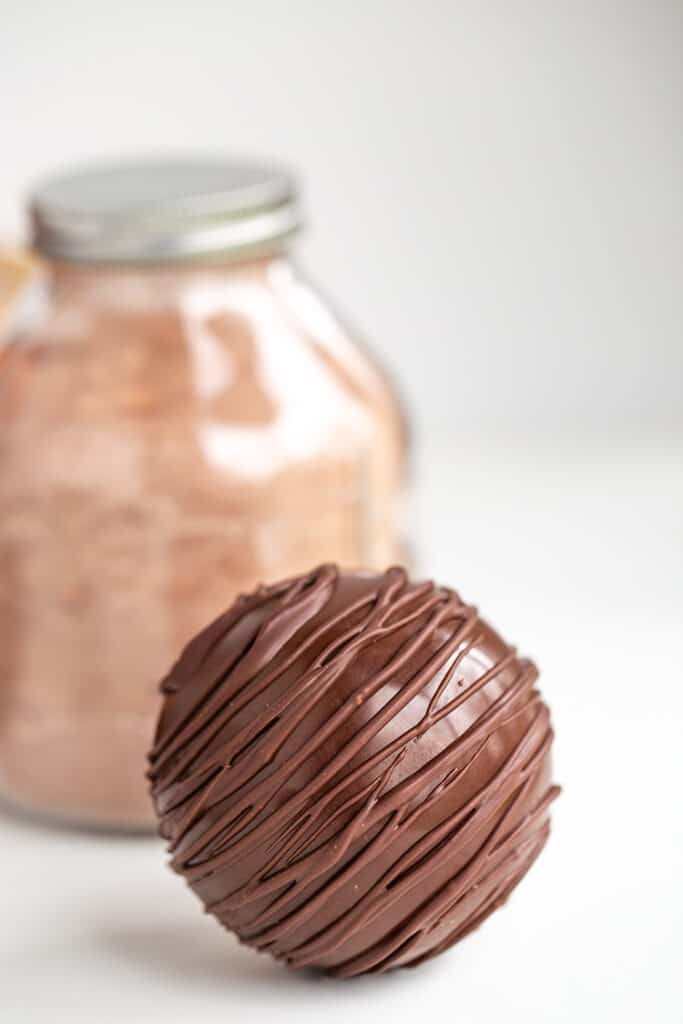 hot chocolate bomb with a jar of hot cocoa mix behind it
