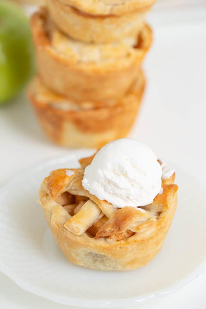mini apple pie with whipped cream on top on a small white plate with a stack of pies behind it