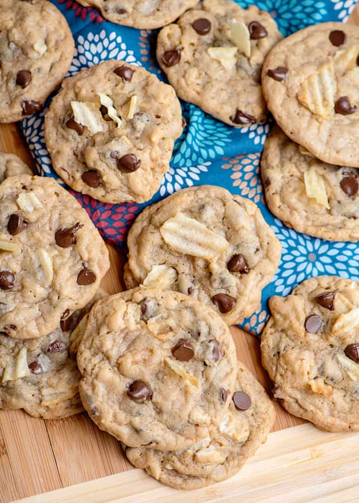 cookies scattered across a cutting board with a blue linen on it