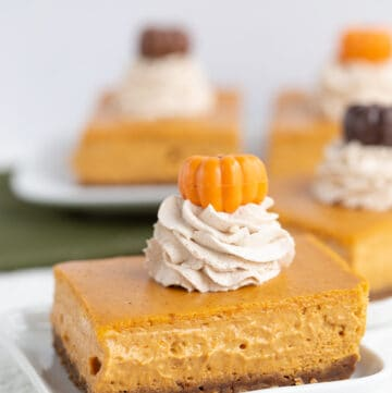 slice of pumpkin cheesecake bars on a white square plate
