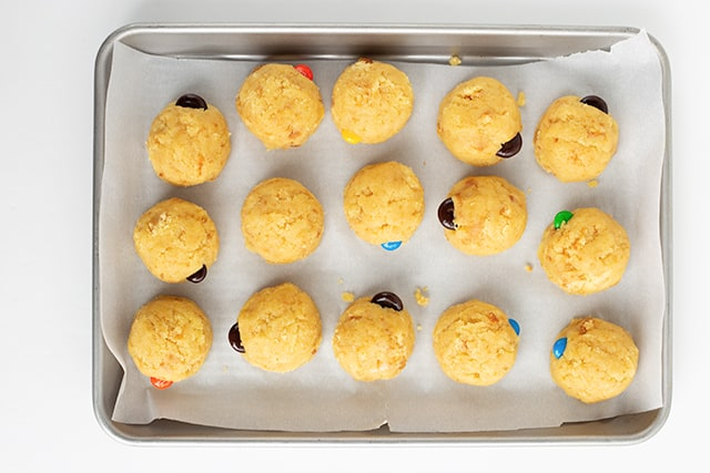 cake pop balls on a baking sheet with parchment paper under them