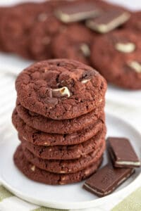 Photo focusing on the top of a stack of cookies that are sitting on a white plate with a green and white fabric under them