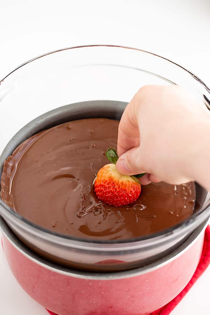 dipping strawberries into a big bowl of melted chocolate chips
