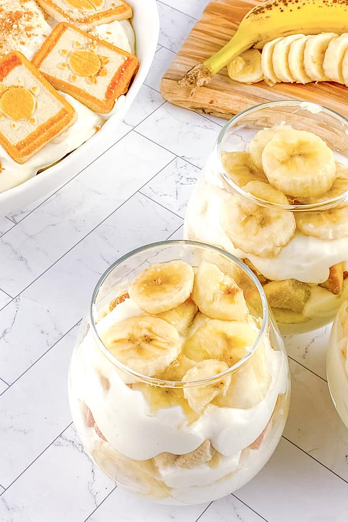 glasses of banana pudding on a white background with a casserole pan and cutting board behind it