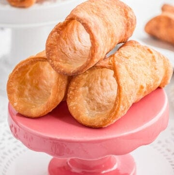 close up of cannoli shells on a small pink stand