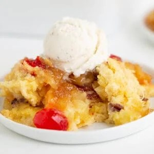 square image of the pineapple upside down dump cake with ice cream on top on a white plate