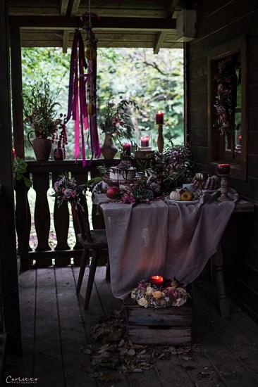 Tisch mit Herbstdekoration und Kuchen und Keramik in violett