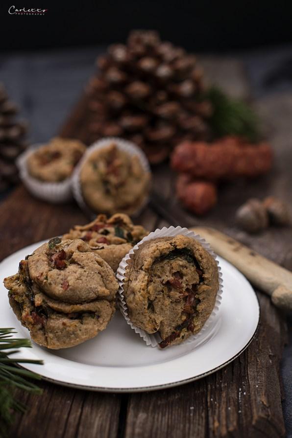 Bruffins auf weißem Teller auf Holzbrett mit Messer, Hauswürstel, Tannenzapfen
