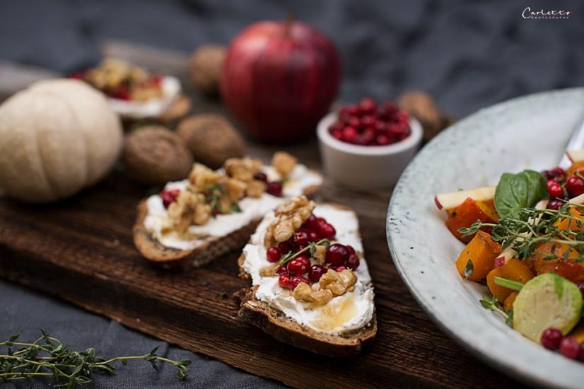 herbstlicher Salat, Brotscheiben mit Ziegenkäse, Nüssen und Preiselbeeren, Nüsse, auf grauem Teller mit braunem Hintergrund, Herbstsalat