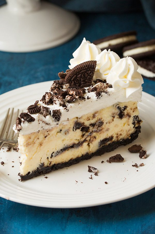 Oreo cheesecake on a white plate set over a blue surface. Cheesecake is made with Oreo crust, cream cheese and Oreo filling and topped with whipped cream.