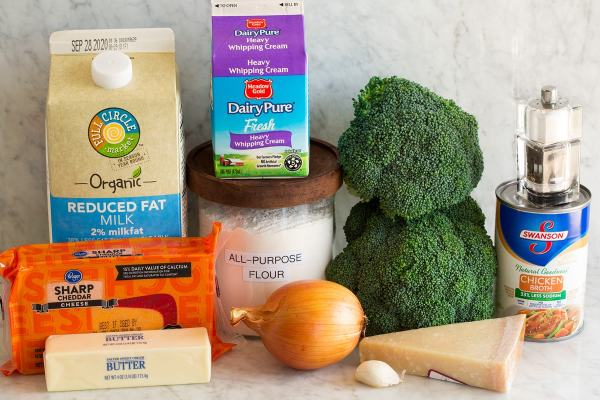 Image of the ingredients that are used to make the broccoli cheese soup. Shows broccoli, hot cheddar cheese, parmesan, butter, onion, garlic, flour, cream, chicken broth, salt and pepper and milk.