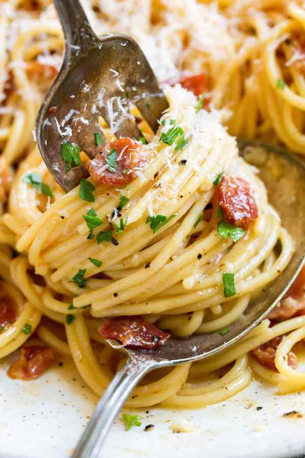 Spaghetti carbonara shown close up swirled around a fork.