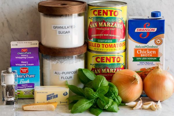 Image of the ingredients used to make homemade tomato soup. Contains canned San Marzano tomatoes, chicken broth, onions, garlic, basil, flour, sugar, butter, parmesan peel, cream, salt and pepper.