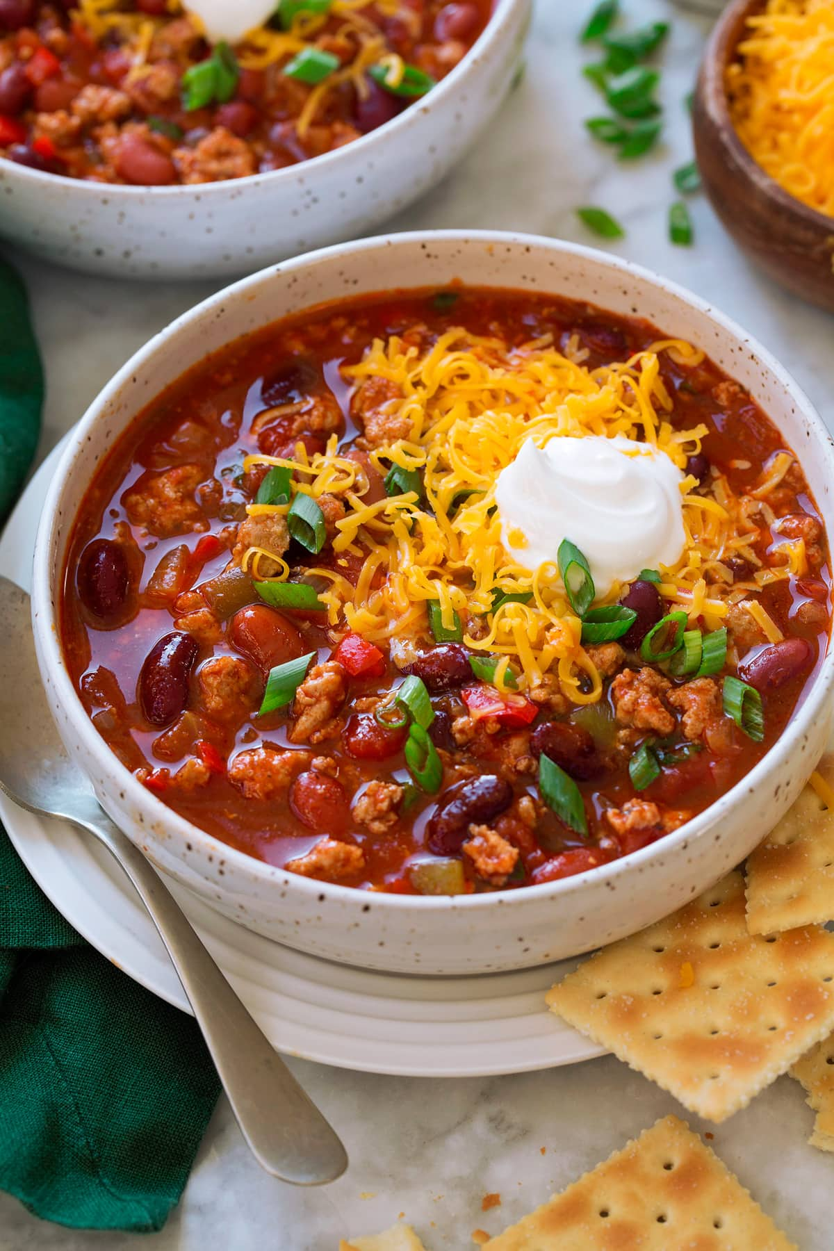 Serving of turkey chili in a white bowl set over a white plate with a spoon and saltine crackers to the side. Chili is topped with shredded cheddar cheese and sour cream.
