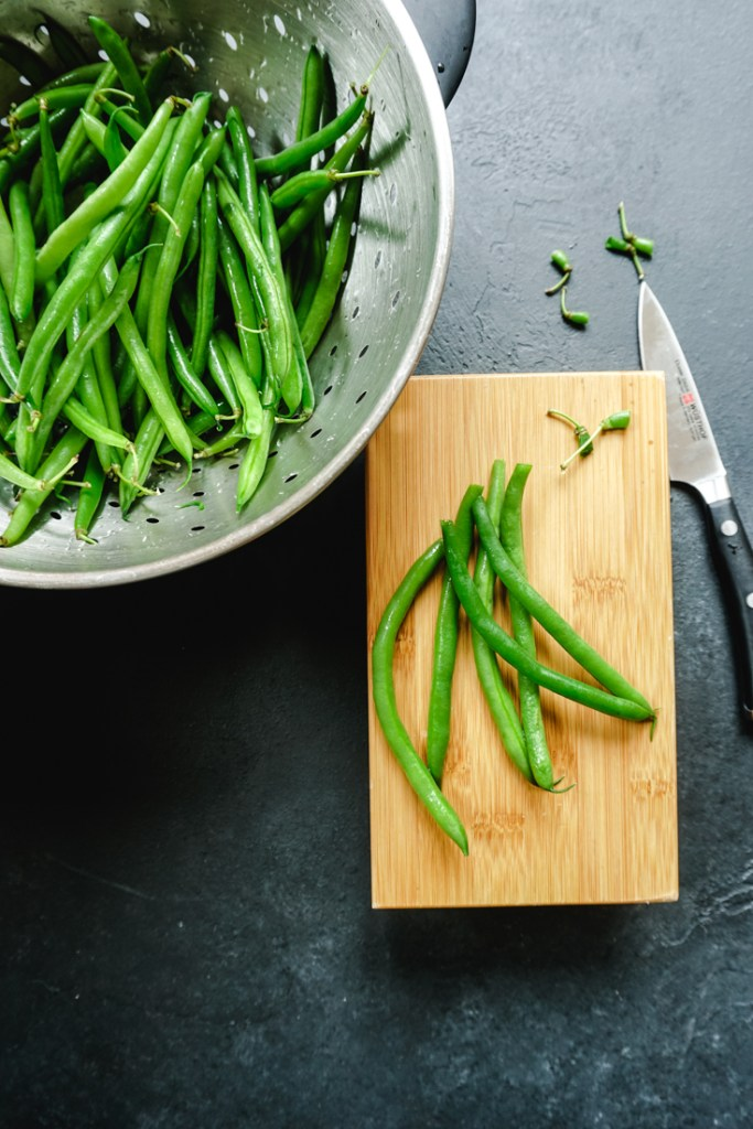 Green beans in a colander and some trimmed beans on a small chopping board