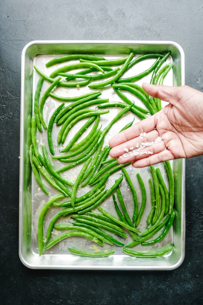Coarse salt in palm of hand over a sheet pan of green beans