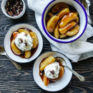 Top shot of Cinnamon Apples in a large white serving bowl and two individual serving size bowls with whipped cream on the cinnamon apples