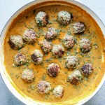 Meatballs in creamy sauce in a white cast iron pan