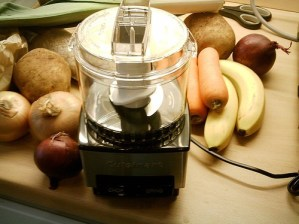 food processor surrounded by carrots and bananas