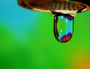 A drop of water from a faucet on a green/blue background