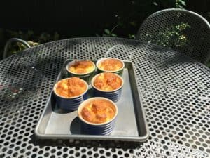 Cheese Soufflés in porcelain ramekins.