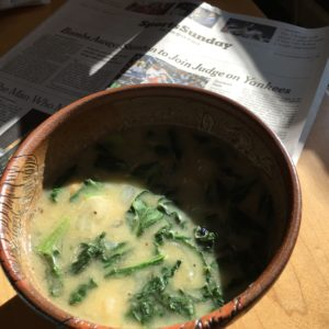 The sports page and a bowl of chickpea soup with spinach and breadcrumbs.