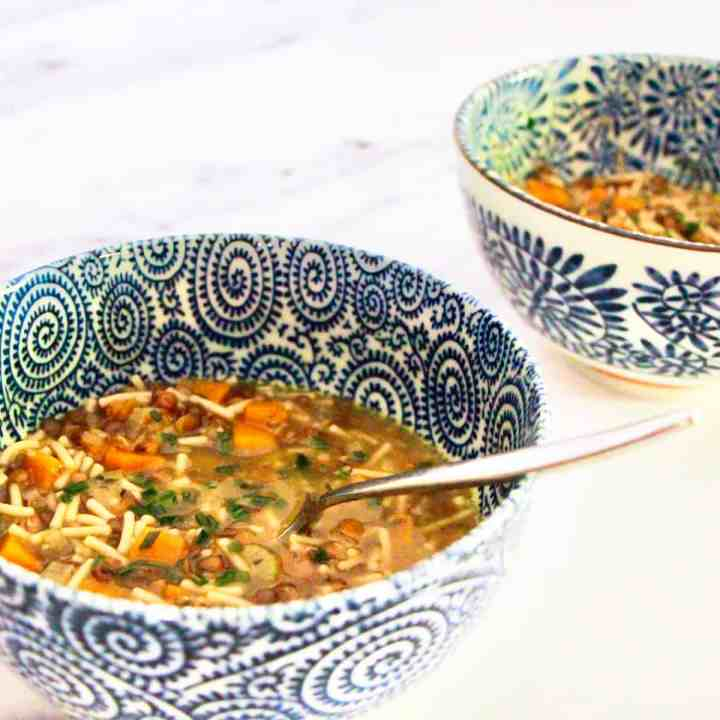 Two blue and white decorated bowls containing veggie noodle soup, spaced with one in front of the other, on a white and grey marble surface.