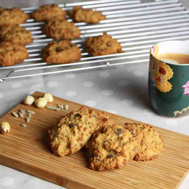 Photo of a chopping board with hazelnut choc-chip cookies on it and cup of coffee in the background with a cooking rack of more cookies behind.