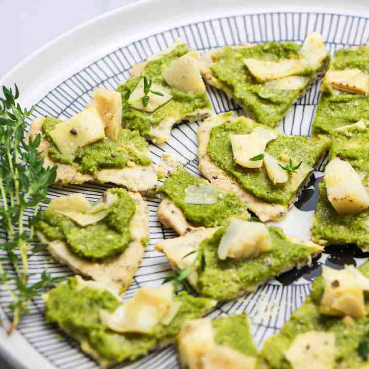 photo of a black and white plate with Artichoke and Tapenade Canapes on it and sprinkled with thyme leaves and a sprig of thyme on the side, on a white and grey marble top.