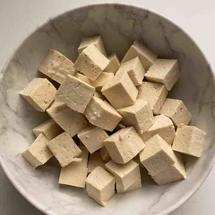 photo of a white bowl full of cubes of raw tofu.