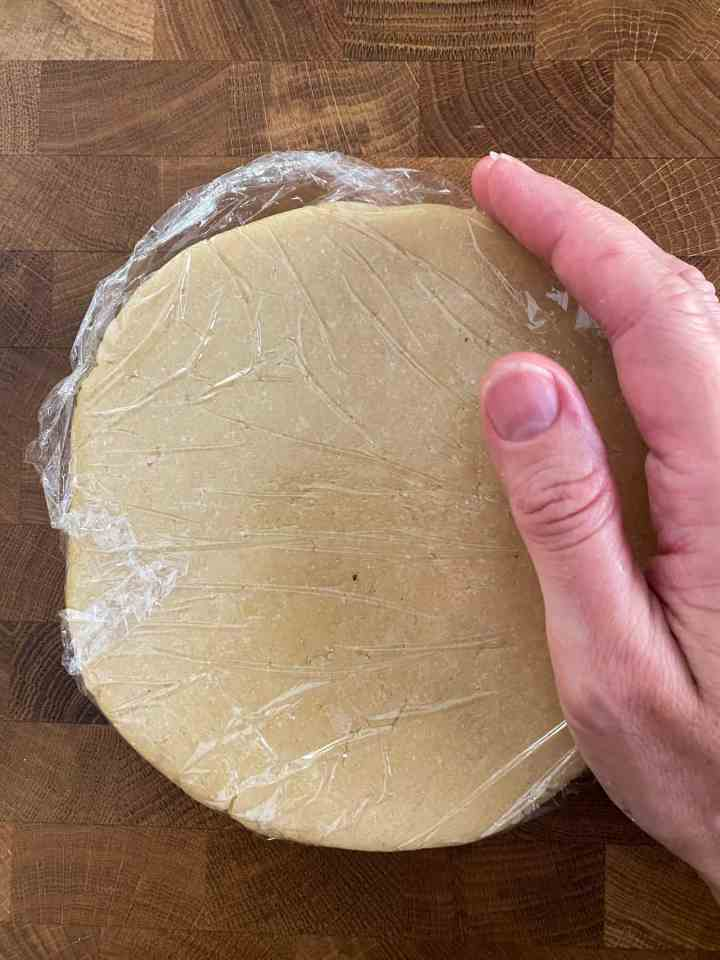 photo of pastry mixture pulled together into a disc shape and wrapped in cling film with a hand alongside showing the size of the disc (adult hand sized).