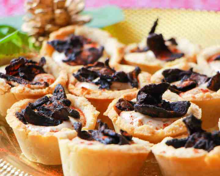 Photo of a plate of mushroom bacon and black garlic cashew cream tartlets