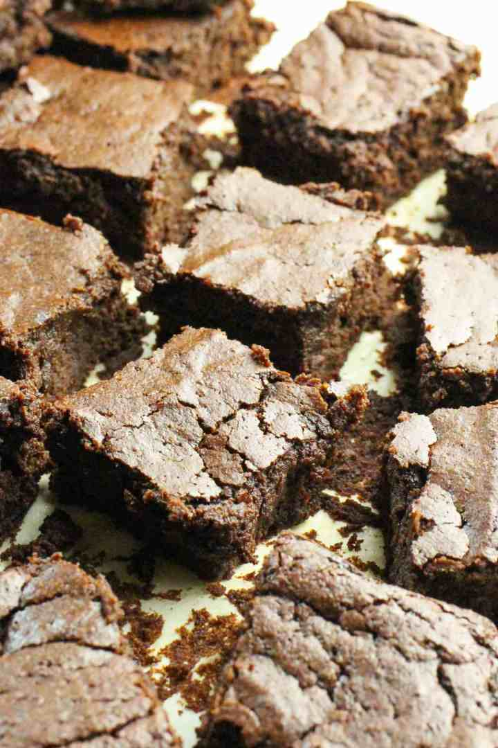 photo of freshly baked chocolate beetroot brownies cut into squares and haphazardly placed on the baking paper they were baked on.
