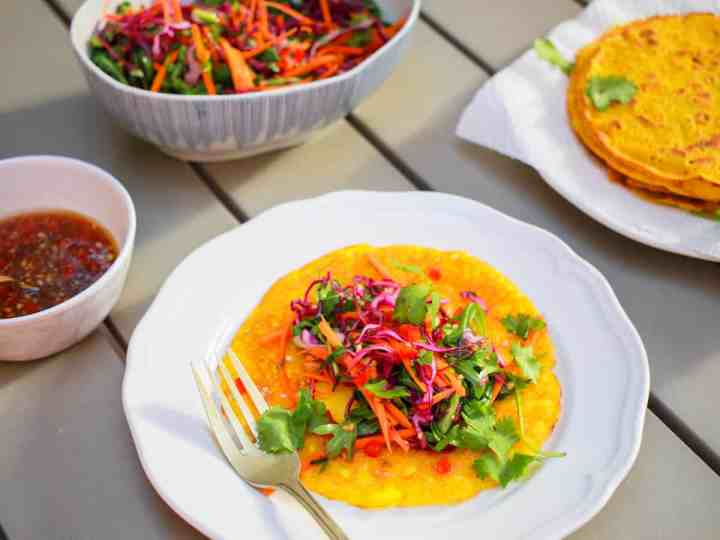 a plate with an open vietnamese coconut pancake with a pile of colourful salad in the middle all set on a grey table outside with a pile of more pancakes in the background.