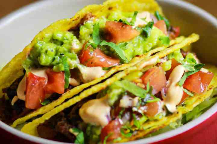 This is a photo of some tacos containing guacamole and salsa