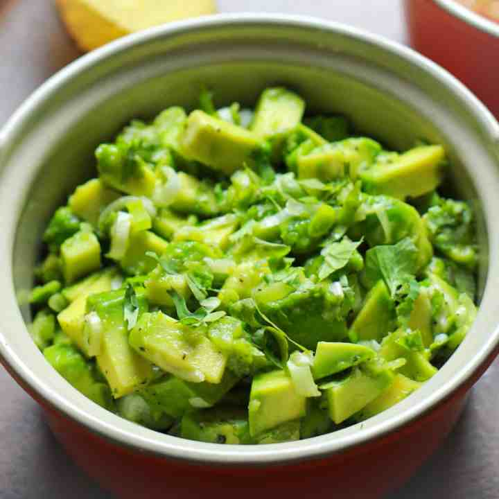Pinterest graphic showing the guacamole in Simple Fresh Guacamole Recipe. This vibrant fresh dip is so simple to make with creamy avocados liberally seasoned and spiked with lime juice. A delicious way to incorporate nutritious avocados into your diet.