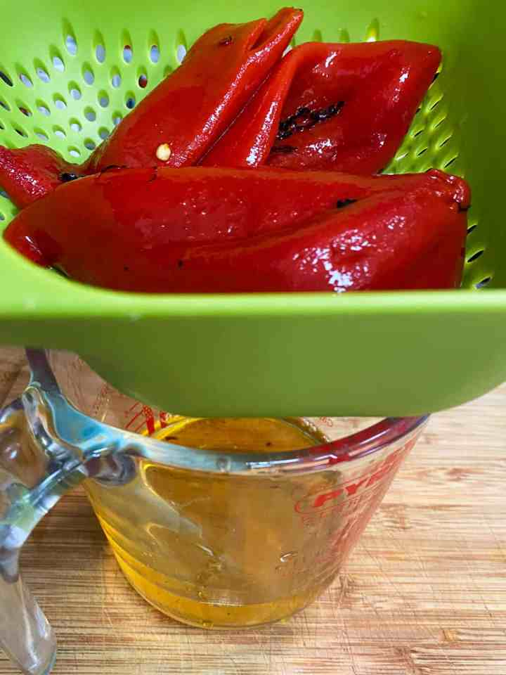 photo of jarred roasted red peppers being drained in a colander over a jug.