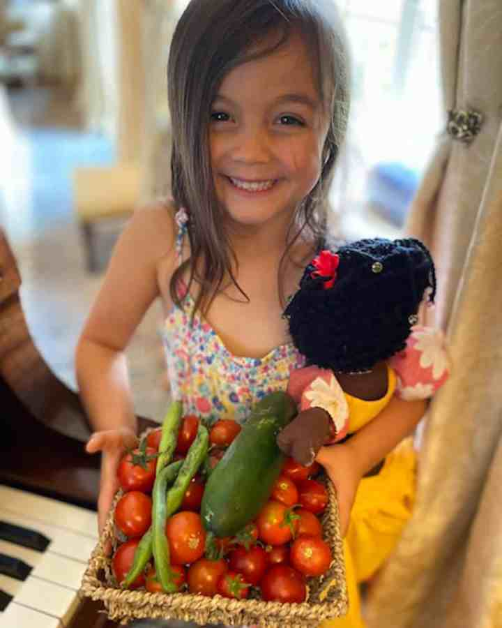 Photo of little girl carrying a basket of tomatoes, a cucumber and 2 spring onions.
