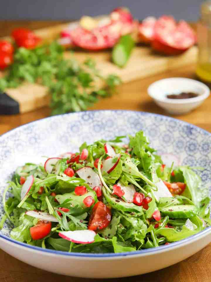 Photo of rocket salad in a pretty blue and white bowl on a wooden tabletop with a chopping board and veggies in the background.