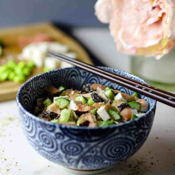 Photo of white marble counter with blue decorated bowl filled with sushi rice and vegan toppings (tofu, cucumber, seaweed, sushi ginger, etc) and flowers and ingredients on a chopping board in the background.