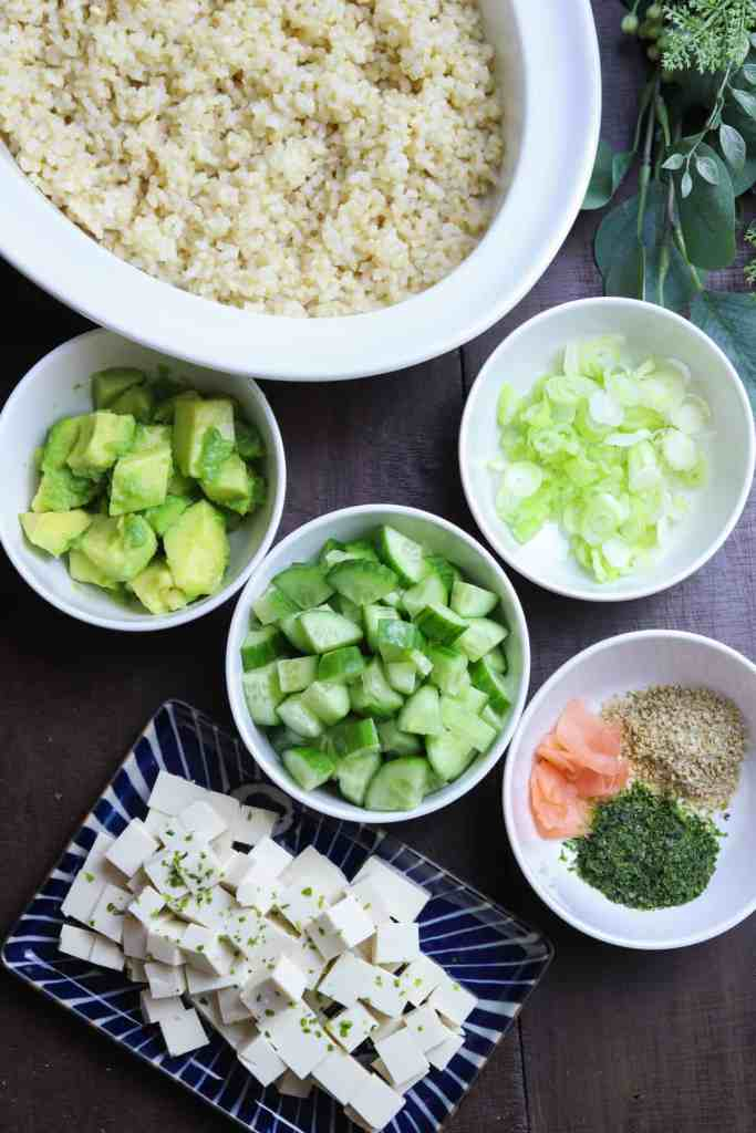 photo of ingredients for vegan sushi bowl in white bowls on a dark wood background