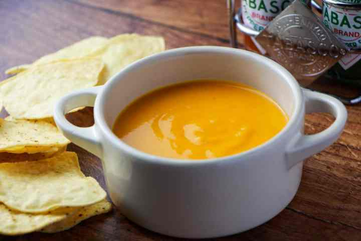 Photo of vegan cheese sauce in a little white ceramic pot with tortilla chips to the side and two types of tabasco in the background, all on a wooden tabletop.