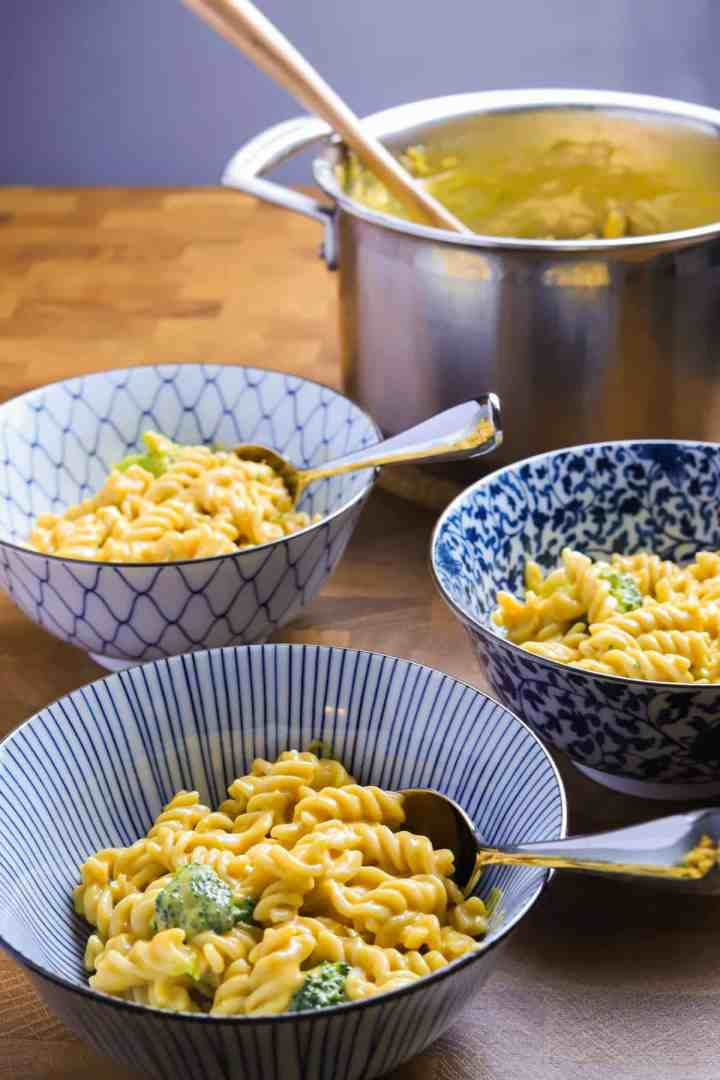 photo of 3 blue and white decorated bowls of vegan mac and cheese on a wooden tabletop with a pan in the background.