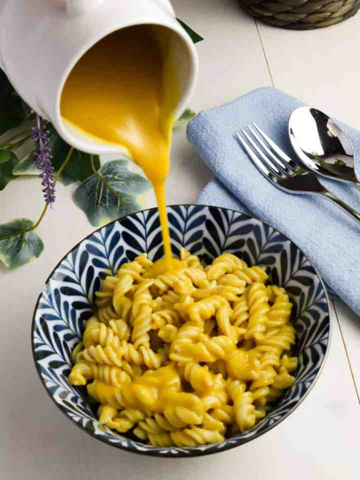 navy and white decorated bowl with mac and cheese in and a white jug pouring over more vegan cheese sauce. All on a white table top with a blue napkin in the background with cutlery on top and some foliage in the back.