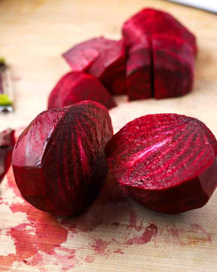 Photo of a peeled beetroot cut in half with some chopped beetroot in the background, on a wooden chopping board stained with beetroot juices.